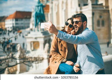 Portrait of loving couple taking selfie in urban enviroment at sunny day