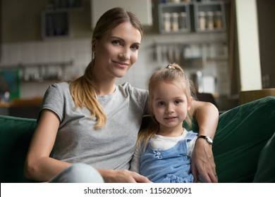Portrait of loving happy family single mother embracing cute little girl sitting on sofa, smiling mom hugging preschool child daughter looking at camera at home, young woman and kid posing indoors