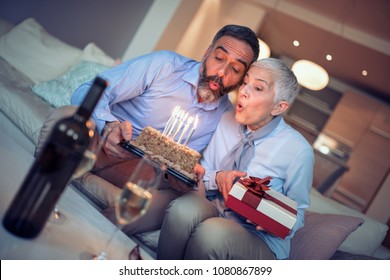 Portrait of loving mature couple celebrating birthday together at home.