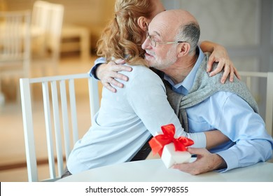 Portrait of loving mature couple embracing happily celebrating holiday together at home, woman hugging gray haired man holding gift box at table