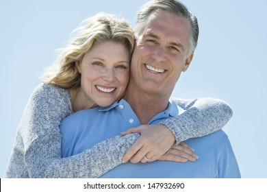 Portrait of loving mature woman embracing man from behind against clear blue sky