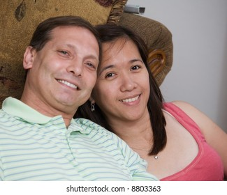 Portrait of a loving mixed race couple, Asian and caucasian smiling sitting in living room inside house
