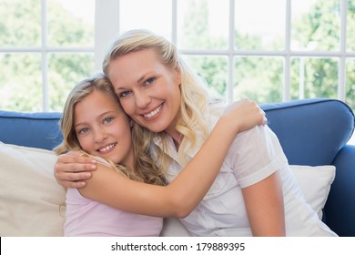 Portrait of loving mother and daughter hugging each other on sofa at home