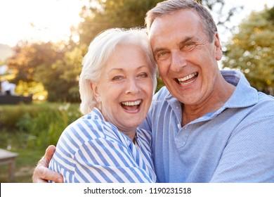 Portrait Of Loving Senior Couple Hugging Outdoors In Summer Park Against Flaring Sun