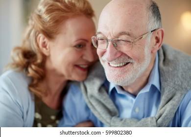 Portrait of loving senior couple sitting close together cuddling caringly and smilingAt home, focus on elderly man wearing glasses