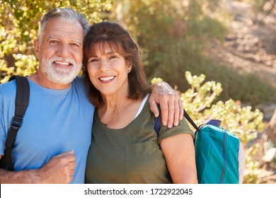 Portrait Of Loving Senior Hispanic Couple Hiking Along Trail In Countryside Together