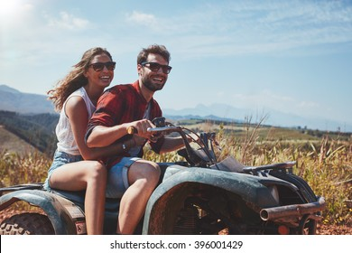 Portrait of loving young couple cruising over country roads by quad vehicle. Happy man and woman driving a quad bike.