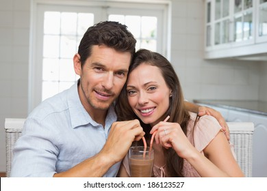 Portrait of a loving young couple sharing a drink at home