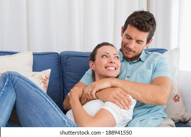 Portrait of a loving young couple sitting on couch at home