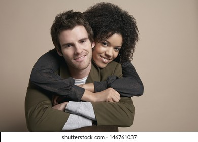 Portrait of loving young couple smiling on colored background