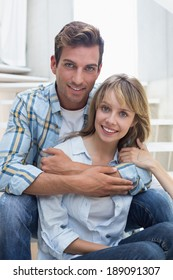 Portrait of a loving young man embracing woman at home