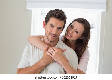 Portrait of a loving young woman embracing man from behind at home