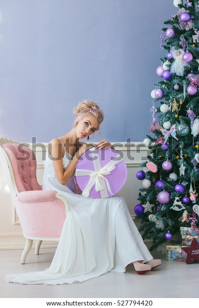 portrait of a luxurious blonde in a white dress sitting on a chair by the Christmas tree round gift box in hand .Christmas.Winter