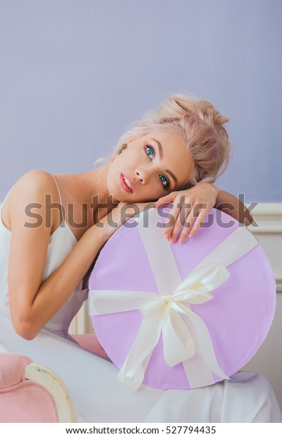 portrait of a luxurious blonde in a white dress sitting on a chair with a round gift box in hand on a lilac background