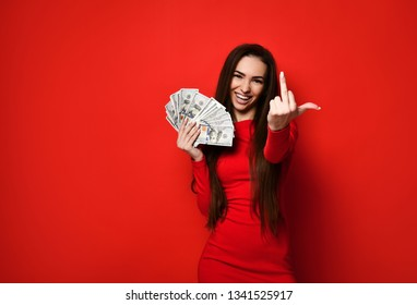 Portrait of a luxurious rich brunette girl in a red dress, holding a fan of  100 dollars , Fuck you!,. isolated over bright red background