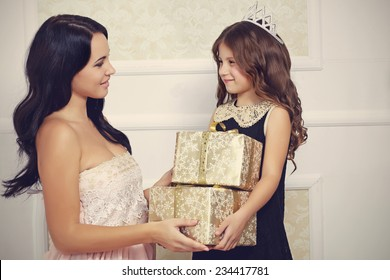 Portrait of luxury family with gold gift boxes
