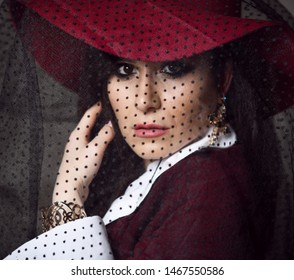 Portrait of luxury high-society woman lady in dark red hat with her veil down looking over her shoulder and touching fixing her hair