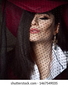 Portrait of luxury noble woman lady in dark red hat with her veil down, closed eyes and hair covering half of her face sends us a kiss