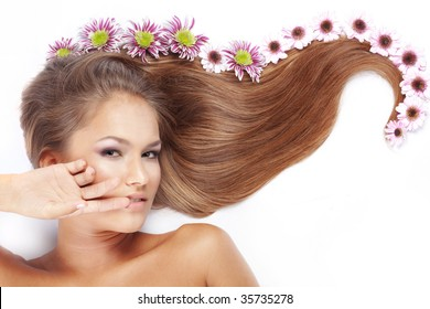 Portrait of lying beautiful female with flowers on her hair