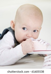 portrait of lying down baby girl holding a shoe