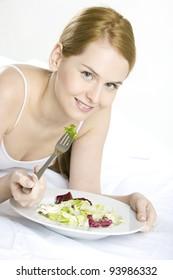 portrait of lying down woman eating salad
