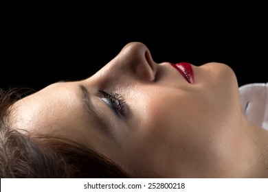 Portrait of lying woman in profile on black background