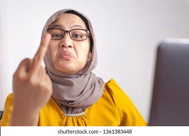 Portrait of mad angry Asian muslim woman shows middle finger gesture, rude businesswoman at the office