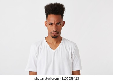 Portrait of mad displesed african american young man with afro hairstyle wears t shirt feels angry and irritated isolated over white background Looks directly in camera