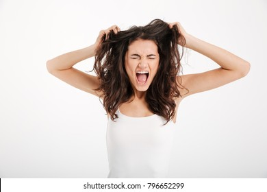 Portrait of a mad girl dressed in tank-top pulling her hair out and screaming isolated over white background