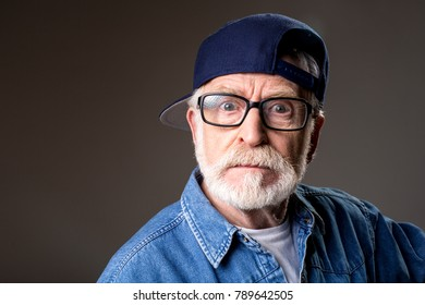Portrait of mad old man in cap looking at camera with wrath. Isolated on grey background