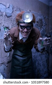 Portrait of a mad scientist with a syringe and a bulb. Halloween concept