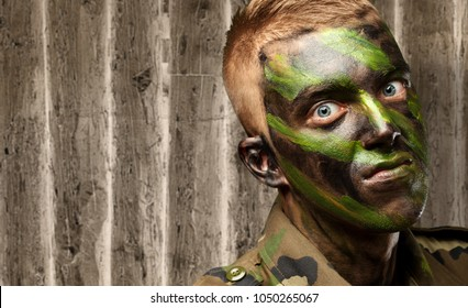 portrait of a mad soldier against an old wooden background