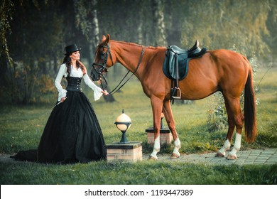 Portrait of magnificent Fashion gothic girl walking a horse .Fantasy art work and fairytale.Amazing brunette model in black-white dress and hat posing.
