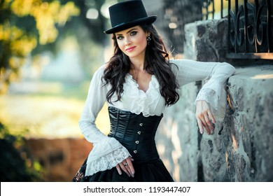 Portrait of magnificent Fashion gothic girl  .Fantasy art work.Amazing brunette model in black white dress and hat posing.Fairytale about young princess