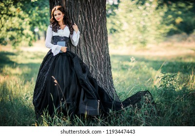 Portrait of magnificent Fashion gothic girl with a book .Fantasy art work.Amazing brunette model in black white dress and hat posing.
