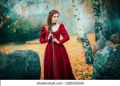 Portrait of magnificent Fashion gothic girl standing in autumn forest .Fantasy art work.Amazing red haired model in claret dress with a sword .Fairytale about young princess-warrior.