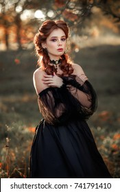 Portrait of magnificent Fashion gothic girl standing in glowing light .Fantasy art work.Amazing red haired model in black dress and hat looking at camera and posing.Fairytale about young princess