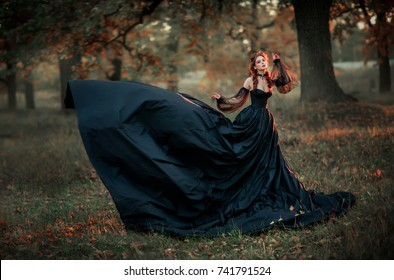Portrait of magnificent Fashion gothic girl sitting near tree .Fantasy art work.Amazing red haired model in black dress and hat looking at camera and posing.Fairytale about young princess