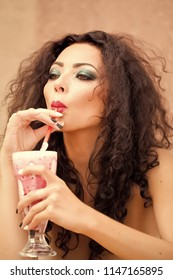 Portrait of magnificent sexy pensive cute young woman with bright makeup brown curly long hair looking away sipping cocktail through straw holding glass on light background, vertical picture