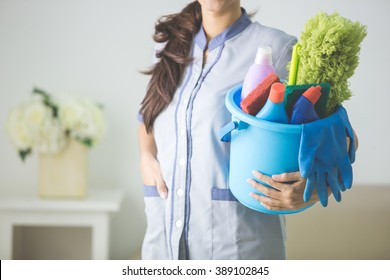 portrait of a maid holding a bucket full of cleaning equipment at home