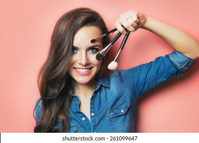 portrait of make up artist woman with makeup brushes near face. beauty concept