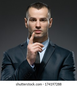 Portrait of making forefinger gesture manager wears business suit and black tie