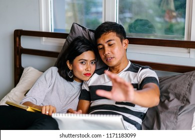 Portrait of a Malay Singaporean couple lying together in bed on a lazy weekend in their HDB flat (government housing). The photo exudes charming hygge and captures an intimate and tender moment.