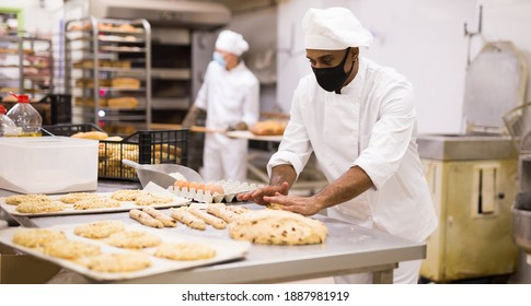 Portrait of male baker in face mask working with dough and forming baguettes