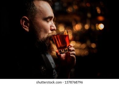 Portrait of male bartender with beard sipping red alcohol cocktail in nightclub