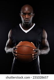 Portrait of male basketball player with a ball over black background. Fit african man in sportswear holding basketball.