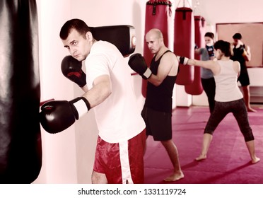 Portrait of male beating punching  bag training in boxing gloves