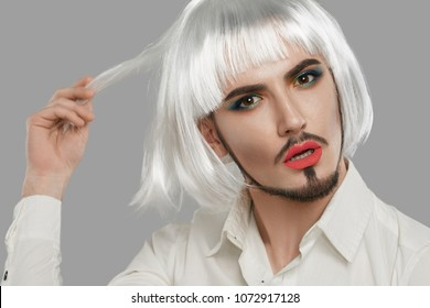 Portrait of a male beauty blogger in button-up shirt, wearing makeup, neat goatee, silver bob wig, neck tattoo. The feminine guy looking at the camera while holding a strand of hair, his lips parted.
