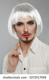 Portrait of a male beauty blogger in a white button-up shirt, wearing green smokey eye makeup, neat goatee, short silver bob wig, neck tattoo. The feminine guy looking at the camera, his hand raised.