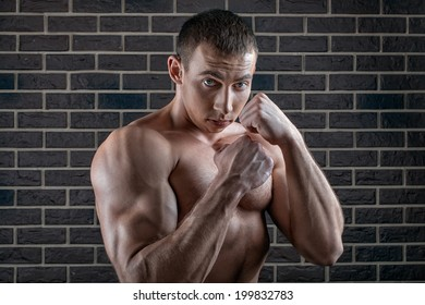 Portrait of a male bodybuilder with fists at the ready.